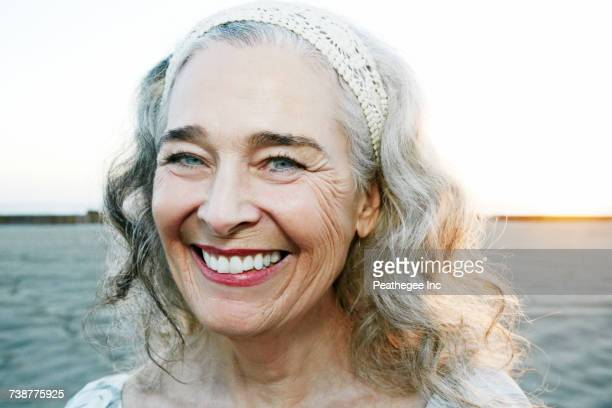 portrait of smiling older caucasian woman at beach - alleen één seniore vrouw stockfoto's en -beelden