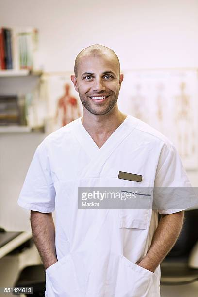 Portrait of smiling orthopedic surgeon standing with hands in pockets in clinic