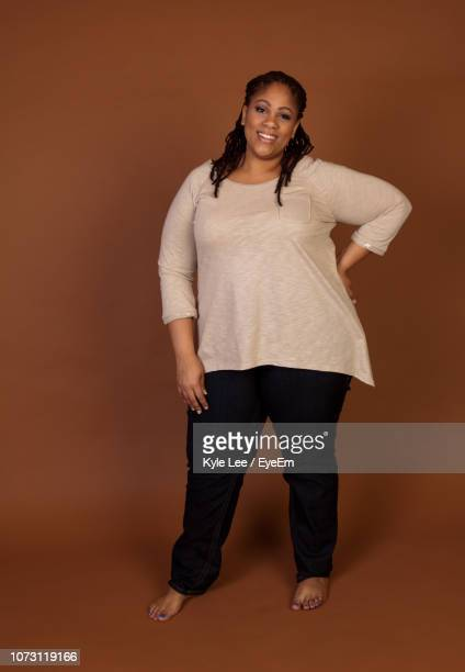 portrait of smiling overweight woman standing over brown background - obese black women photos et images de collection