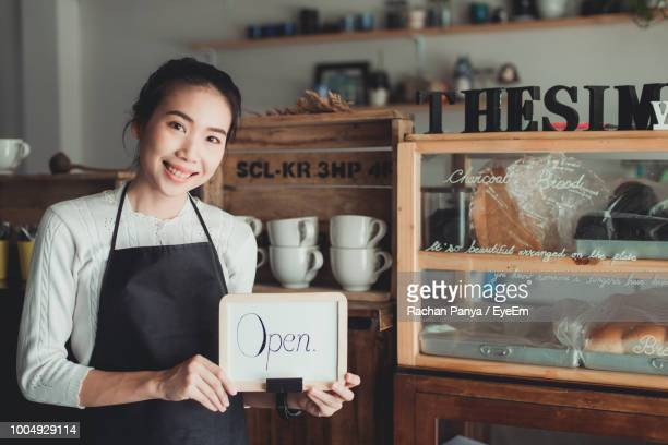 Portrait Of Smiling Owner Holding Sale Text On Whiteboard In Store