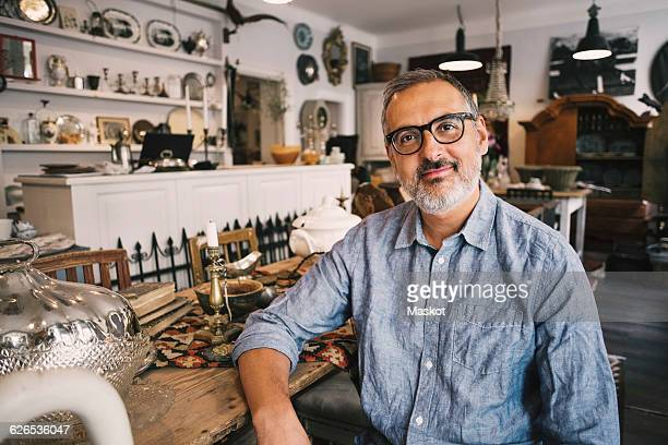 Portrait of smiling owner sitting at table in antique store