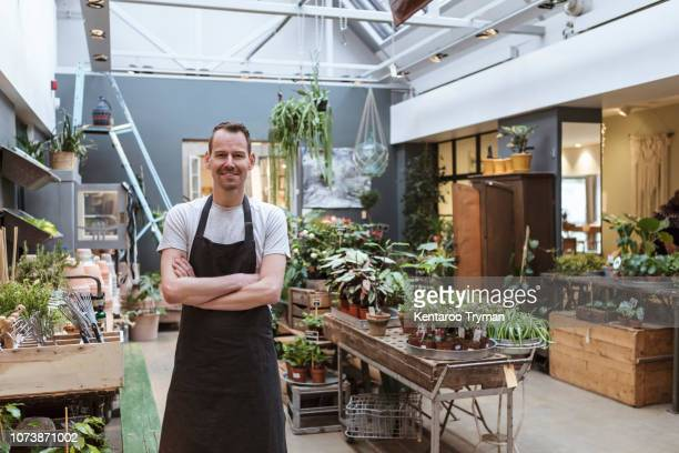 portrait of smiling owner standing with arms crossed against potted plants at store - entrepreneur stockfoto's en -beelden