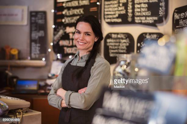 Portrait of smiling owner wearing apron standing at store