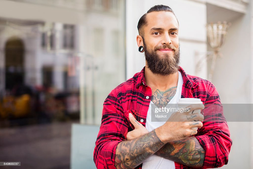 Portrait of smiling owner with coffee outside candy store : Stock Photo