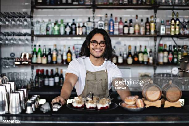 Portrait of smiling owner with food standing at counter in restaurant