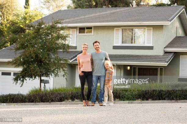 portrait of smiling parents with boy standing in front of their home - wohnhaus stock-fotos und bilder