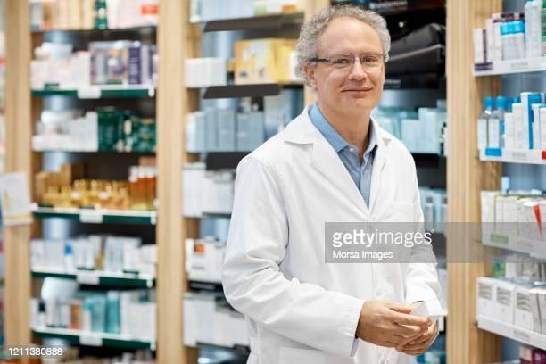portrait of smiling pharmacist holding medicine - farmacêutico imagens e fotografias de stock