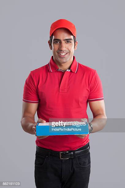 Portrait of smiling pizza delivery man against gray background