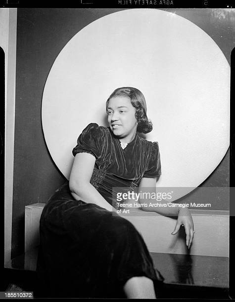 Portrait of smiling Pocahontas G Crews wearing dark velvet dress with triangular brooch posed leaning in front of light colored circular background...