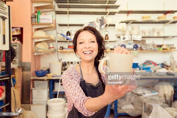 Portrait of smiling potter in studio holding jug