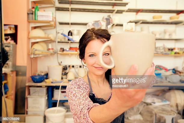 portrait of smiling potter in studio holding jug - 40 44 jaar stock pictures, royalty-free photos & images