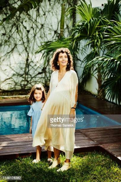 portrait of smiling pregnant mother holding hands with young daughter in courtyard by pool - role model stock pictures, royalty-free photos & images
