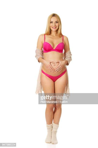Portrait Of Smiling Pregnant Woman In Bikini Standing Against White Background