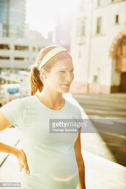 Portrait of smiling pregnant woman on city street before morning run