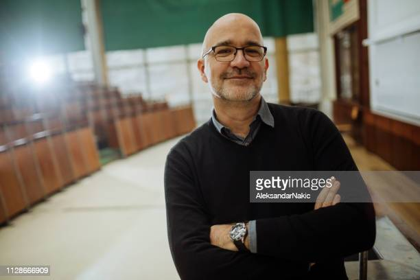 portrait of smiling professor in the amphitheater - showing stock pictures, royalty-free photos & images