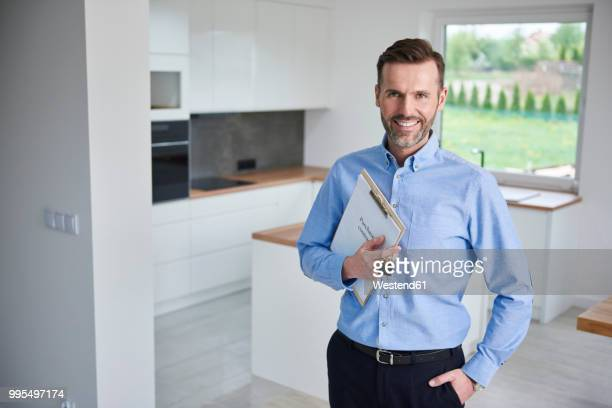 portrait of smiling real estae agent in new apartment - real estate agent stock pictures, royalty-free photos & images