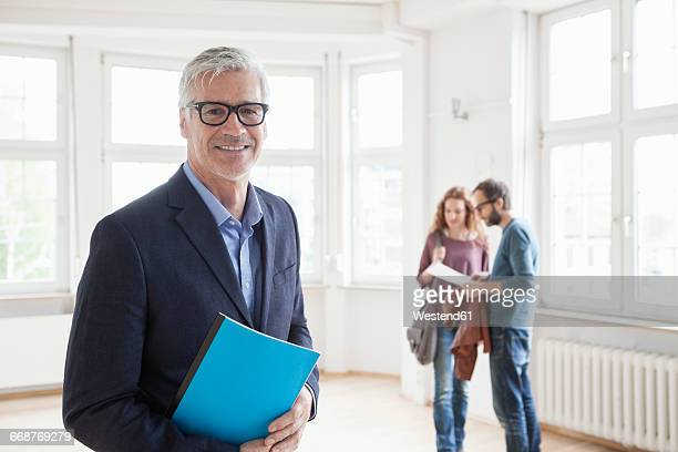 Portrait of smiling real estate agent with couple in background