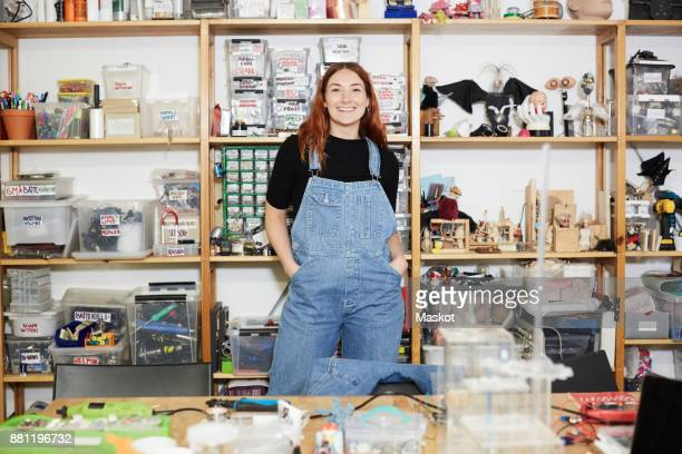 Portrait of smiling redhead engineer standing with hands in pockets against shelf at workshop
