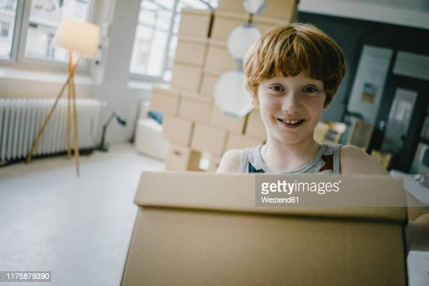 portrait of smiling redheaded boy with cardboard box - wishful skin stock pictures, royalty-free photos & images