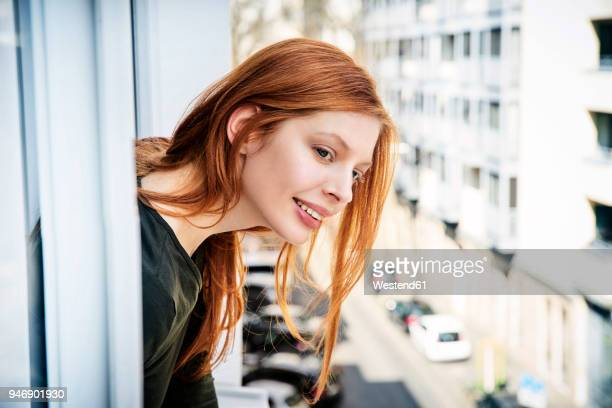 portrait of smiling redheaded woman leaning out of window - neugierde stock-fotos und bilder