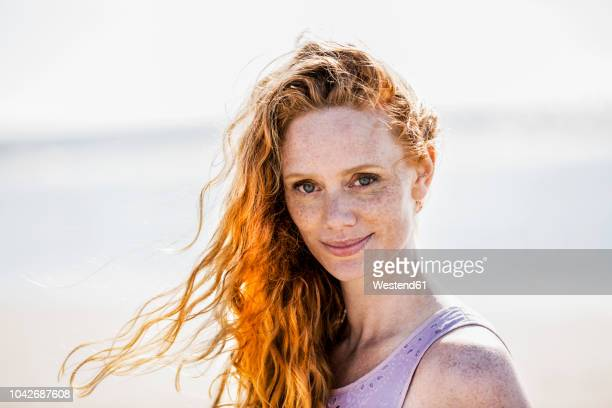 portrait of smiling redheaded woman outdoors - redhead stock pictures, royalty-free photos & images