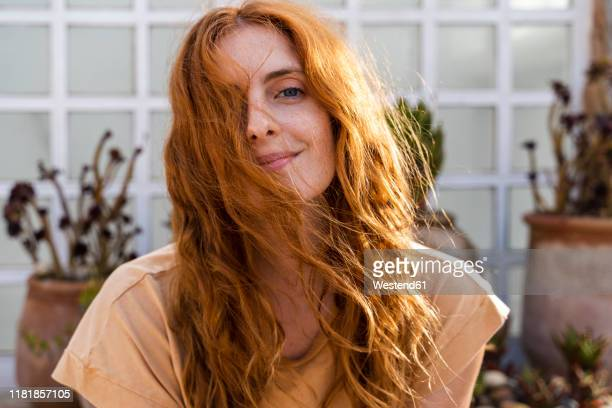 portrait of smiling redheaded young woman on terrace - mooie mensen stockfoto's en -beelden