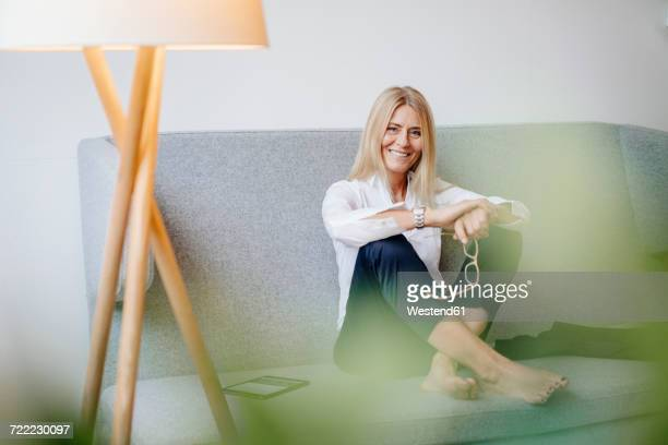 portrait of smiling relaxed businesswoman sitting on couch - variable schärfentiefe stock-fotos und bilder