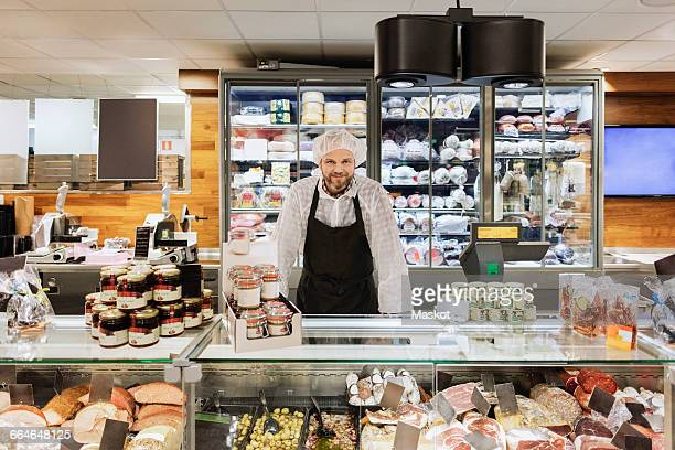 portrait of smiling sales clerk standing in supermarket - delicatessen stock pictures, royalty-free photos & images
