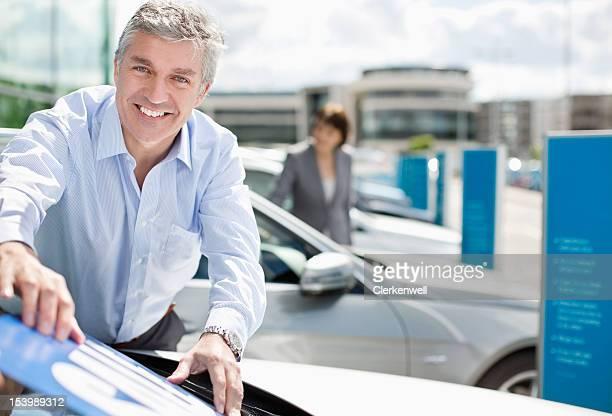 Portrait of smiling salesman placing sale sign on car in car dealership parking lot