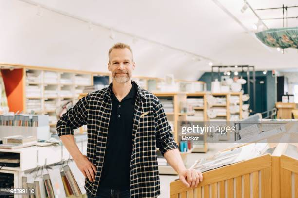portrait of smiling salesman standing in store - hand on hip stock pictures, royalty-free photos & images