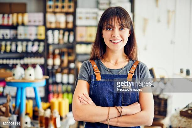 portrait of smiling saleswoman standing arms crossed in deli - delicatessen stock photos and pictures