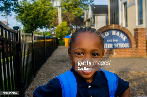 Portrait of smiling schoolboy at school gate
