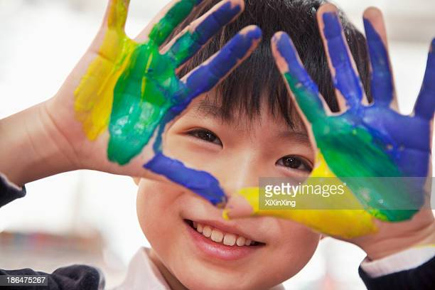 Portrait of smiling schoolboy finger painting, close up on hands