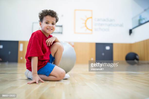 portrait of smiling schoolboy with gym ball in gym class - physical education stock pictures, royalty-free photos & images