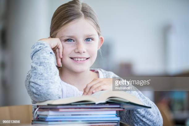 portrait of smiling schoolgirl with books in school - kind im grundschulalter stock-fotos und bilder