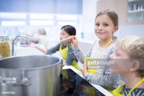 portrait of smiling schoolgirl with classmtes in cooking class - nur kinder stock-fotos und bilder
