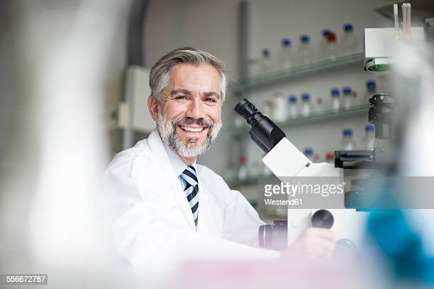 Portrait of smiling scientist in laboratory with microscope