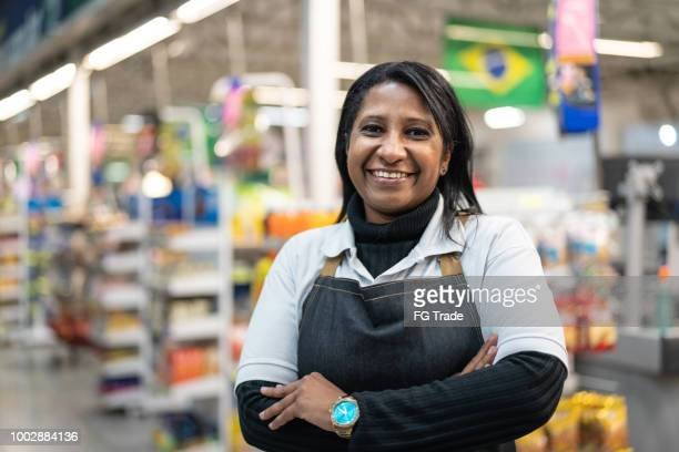 portrait of smiling seller of a supermarket - convenience store stock pictures, royalty-free photos & images
