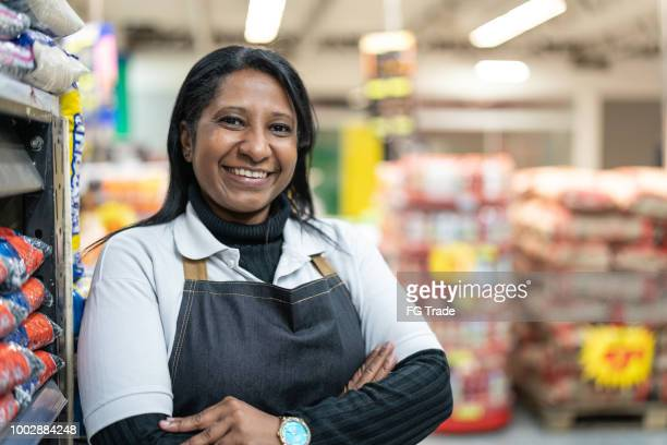 portrait of smiling seller of a supermarket - convenience store stock photos and pictures