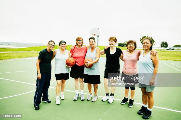 Portrait of smiling senior and mature women standing on outdoor basketball court after game