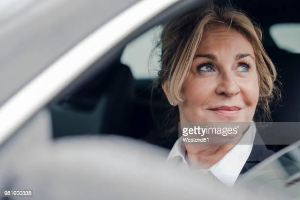 portrait of smiling senior businesswoman in car - conductor oficio fotografías e imágenes de stock