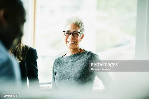 portrait of smiling senior businesswoman in discussion with coworkers - weibliche angestellte stock-fotos und bilder