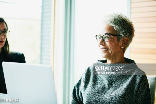portrait of smiling senior businesswoman in meeting in office conference room - disruptagingcollection stock photos and pictures