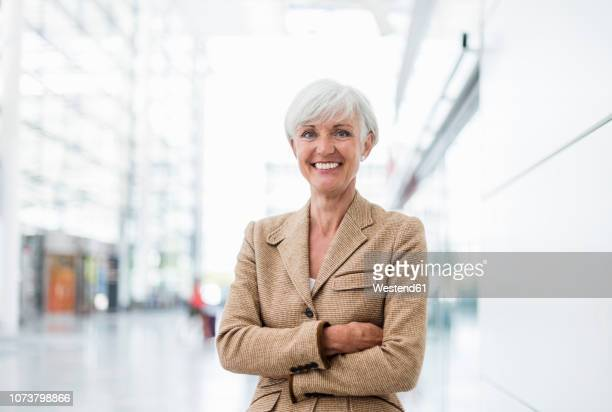 portrait of smiling senior businesswoman - brown jacket stock pictures, royalty-free photos & images