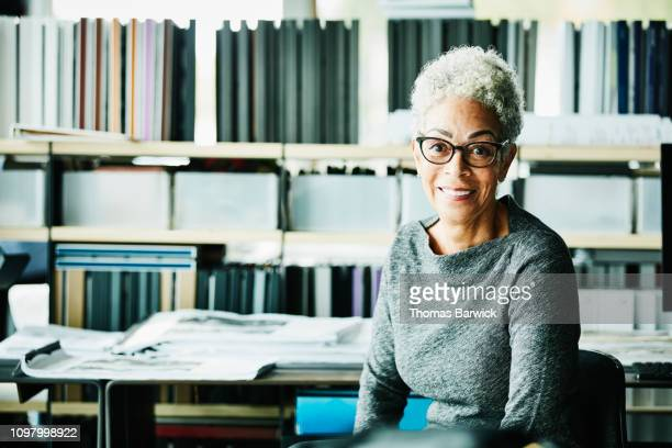 portrait of smiling senior businesswoman seated at workstation in design studio - businesswear stock pictures, royalty-free photos & images