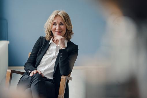 Portrait of smiling senior businesswoman sitting in chair - gettyimageskorea
