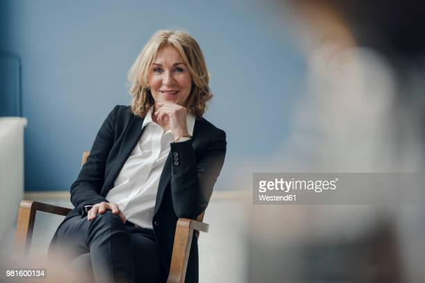 portrait of smiling senior businesswoman sitting in chair - zakenvrouw stockfoto's en -beelden