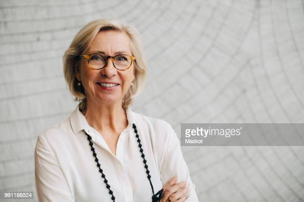 portrait of smiling senior businesswoman standing against wall in office - alleen één seniore vrouw stockfoto's en -beelden