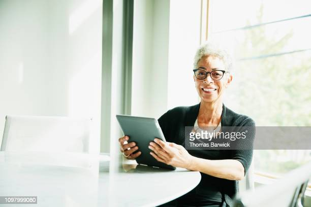 portrait of smiling senior businesswoman working on digital tablet in office conference room - white hair stock pictures, royalty-free photos & images