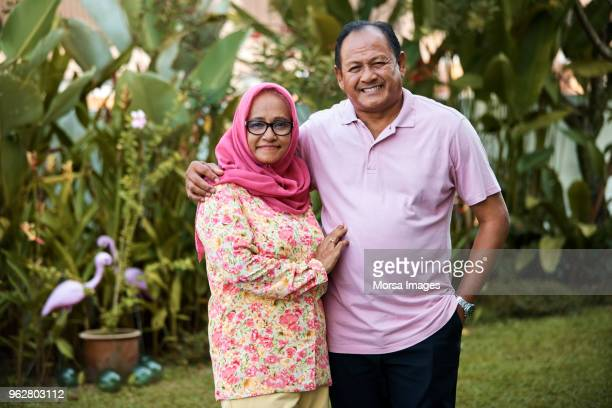 portrait of smiling senior couple in yard - muslim couple stock pictures, royalty-free photos & images